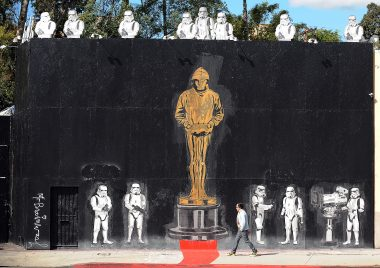 "A man walks in front of a mural celebrating Banksy's Academy Award achievement signed by Mr. Brainwash in Los Angeles, California on February 17, 2011. Banksy is nominated for best documentary for ""Exit Through the Gift Shop"" at the Oscars, due to be announced on February 27 at the climax of Tinseltown's annual awards season.  AFP PHOTO / GABRIEL BOUYS (Photo credit should read GABRIEL BOUYS/AFP/Getty Images)"